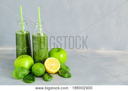 Green Smoothie in Bottles and some Fresh ingredients: apples,cucumber, spinach, selery,bananas,milk, lime and lemon with Honye and Green Tea.