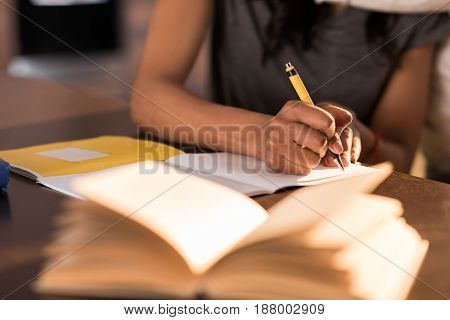 partial view of woman sitting at table and writing in notebook at home
