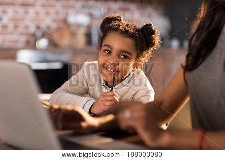 Portrait Of Little Girl Doing Homework With Mother Using Laptop Near By