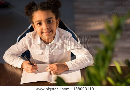 High Angle View Of Little Girl Sitting At Table At School
