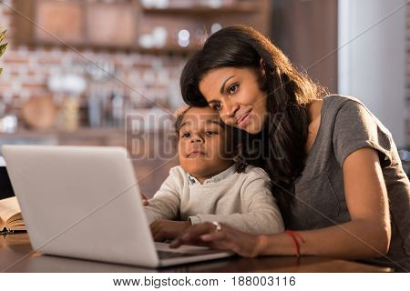 Portrait Of Smiling Mother And Daughter Using Laptop At Home