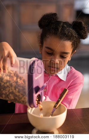 Portrait Of Focused Girl Filling Bowl With Flakes At Breakfast