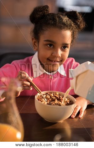 Portrait Of Smiling Little Girl Having Breakfast At Home