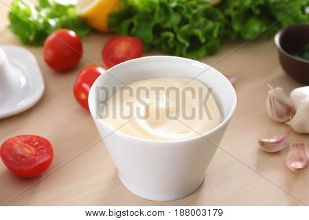 Delicious mayonnaise in bowl on kitchen table, closeup