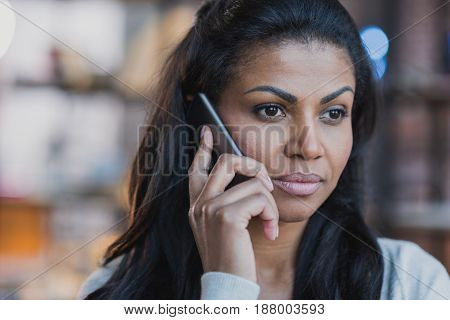 Close Up Portrait Of Young African American Woman Talking On Smartphone At Home