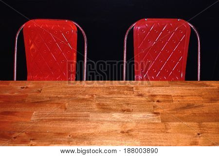 two vintage red metal chairs against black wall in front of pine wooden table