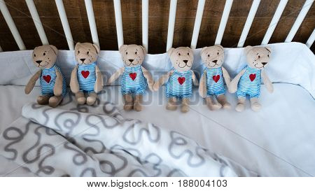 Six sweet teddy bears on baby cot.