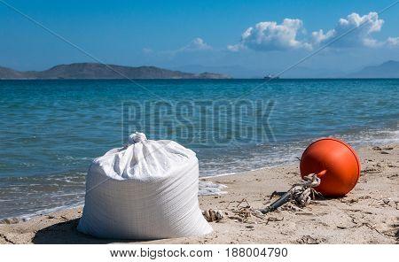 Sandbag as an anchor of a red signal buoy lay at coastline.