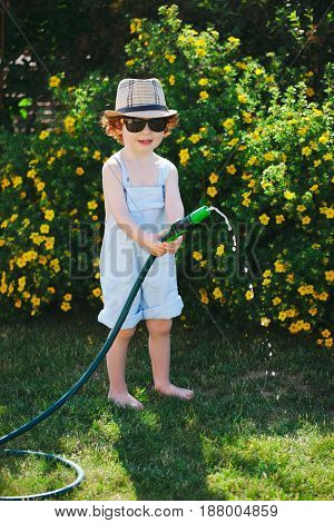 cute little boy watering the garden with hose
