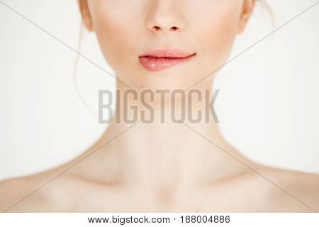Close up of young beautiful girl with clean healthy skin biting lip over white background. Copy space. Cosmetology and spa.