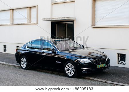 STRASBOURG FRANCE - 26 APR 2017: Modern black luxury BMW hybrid limousine car on the street of Strasbourg France with beautiful houses in the background with diplomatic plates