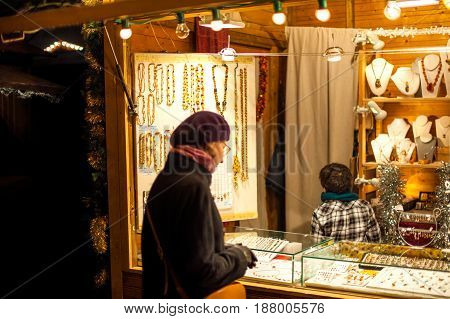 STRASBOURG FRANCE - DEC 23 2016: Woman buying traditional Christmas toys from the Christmas market stall at the Christmas Market in France Strasbourg Alsace