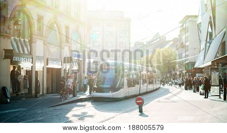 STRASBOURG FRANCE - APR 3 2017: Busy center of the French city of Strasbourg Alsace with tramways and commuters pedestrians walking under architectural station l'Homme de Fer on a sunny evening with sun flare