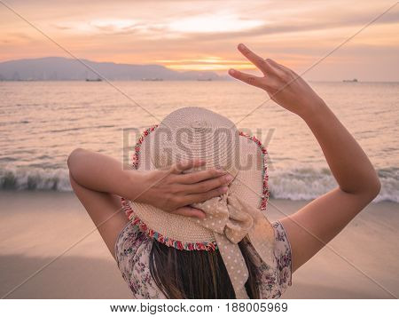 woman holds two fingers or Victory Sign on the beach during sunset showing encouragement when we are discouraged.