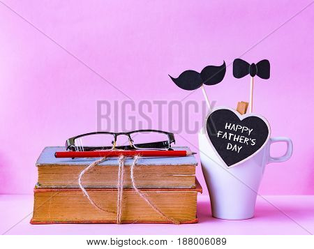 Father's day concept. Happy father day text on stack of books gifts tea cup with black Mustache on pink background