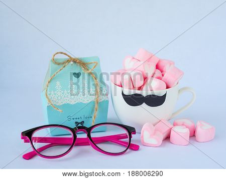 Father's day concept. Sweet love box with glasses and sweet marshmallow in the shape of heart in cup with black Mustache on white background