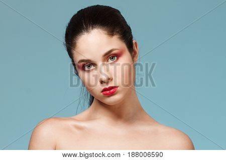 Fashion portrait of young beautiful nude girl with bright make up looking at camera. Copy space.