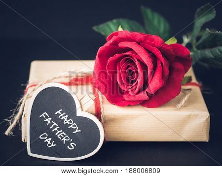 Father's day concept. Happy Father's Day message with red rose on black background