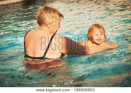 grandmother teaching little girl to swim, active family