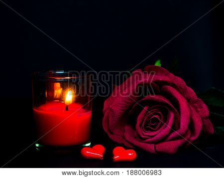 Low key of Valentines Day background-red rose with red candle and two red hearts