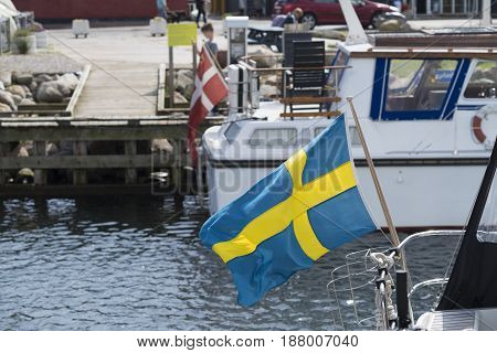 small swedish flag on a yacht in the Hundested harbor in Denmark