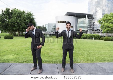 Two businessmen or workers in black suit with tie and shirt with beard standing in front of an office building. One shows success, happiness, smile, celebration, win and other disappointment, sadness.