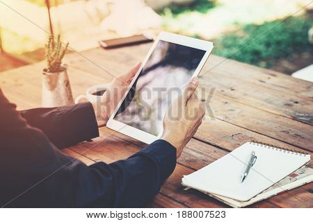 Asia Business Man Holding Tablet On Table In Coffee Shop With Vintage Toned Filter.