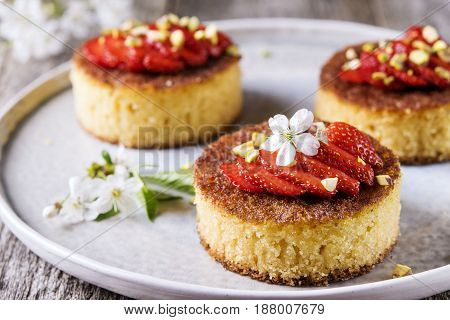 Pieces of homemade sponge cake with strawberry and pistachio decorated flowers of cherry on a rustic vintage wooden table. Selective focus