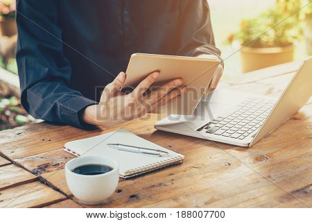 Asia Business Man Using Tablet And Laptop On Table In Coffee Shop With Vintage Toned Filter.