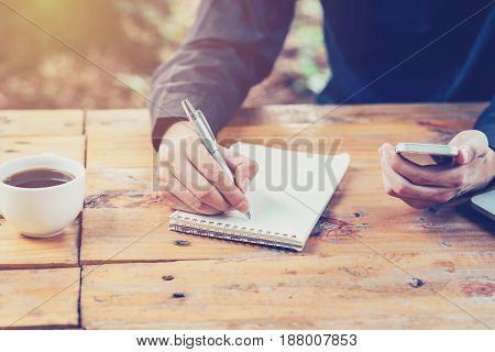 Asia Business Man Hand Writing Notebook Paper And Using Phone On Wood Table In Coffee Shop With Vint