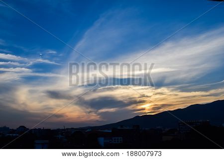 Mountain terrain city on cloudy sky with sunlight beam. Beautiful panoramic view of highland.