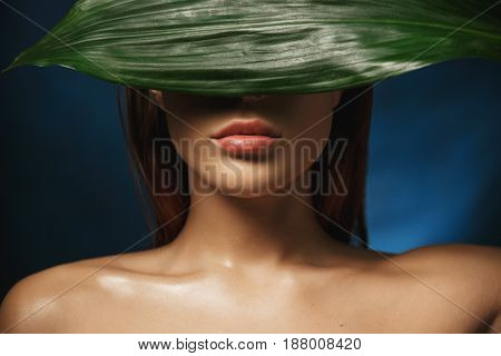 Young naked woman with beautiful collarbone hiding face behind fresh green leave. Beauty photography.
