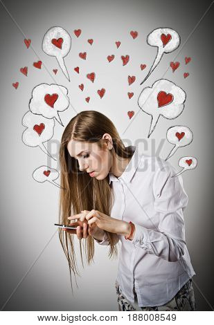 Woman in white is using a mobile phone. Valentine day.