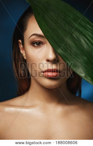 Beauty and fashion photography concept. Naked woman covering left eye with green leaf. Dark background.