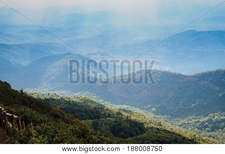 Mountain terrain in a sea of mist on cloudy sky with sunlight beam. Beautiful panoramic view of highland.