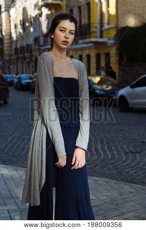 Portrait of beautiful brunette girl in a modern city wearing fashion dress. Trend look