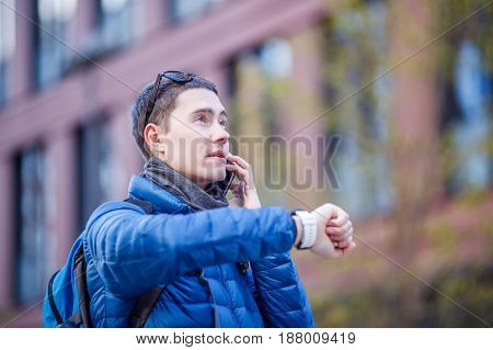 Man talking on phone and looking at smartwatch in the city