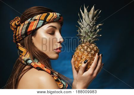 Side view of attarctive woman with bandana on forehead holding pineapple in hands. Exotic concept.