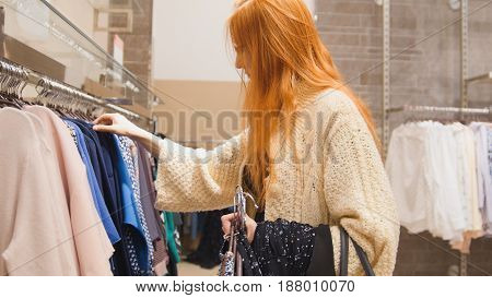 A red-haired young woman chooses dress in shop