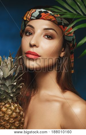 Nude style. Beautiful shirtless woman standing under green leaves holding pineapple and looking at camera.