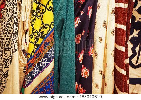 Seven different fabrics of various designs, patterns, and colors, draped in a row together.