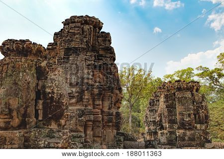 Smiling stone faces of Prasat Bayon the central temple of Angkor Thom Complex, Siem Reap, Cambodia. Ancient Khmer temple is surrounded by tropical trees famous Cambodian landmark, World Heritage.