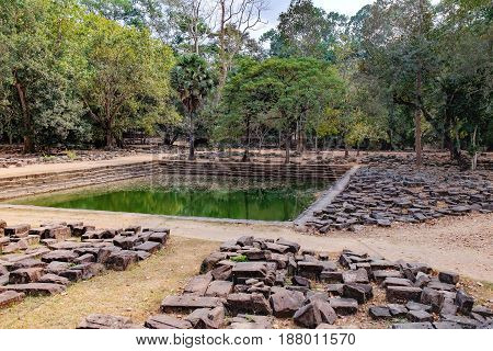 Small artificial lake of Baphuon Temple in Angkor Complex, Siem Reap, Cambodia. Pile of stones on road to pond in foreground. Ancient Khmer architecture and famous Cambodian landmark, World Heritage