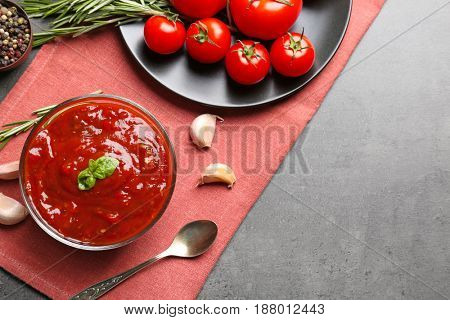 Delicious ketchup in bowl with ingredients on dark background, top view