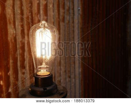 Antique style light light bulb on rusty wall background.