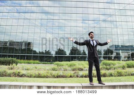 Successful happy smiling cheerful arabic businessman or worker in black suit with tie and shirt with beard standing in front of an office building with raised hands on green grass in summer day.