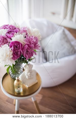 Summer home decoration, bouquet of fresh pink peonies on coffee table in white room interior.