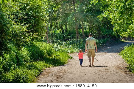 Father and his little daughter walking hand in hand together on a sandy path in the forest. It is a warm and sunny day in the spring season.