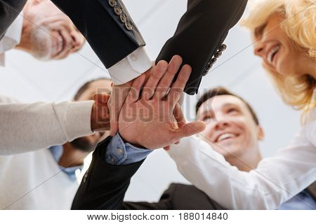 Team spirit. Happy delighted positive people standing in the circle and holding their hands together while showing their unity