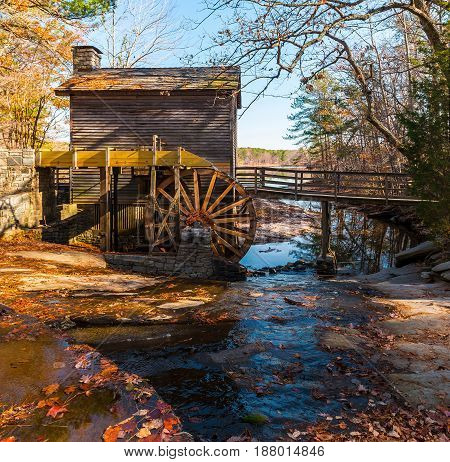 Grist Mill and creek flowing into the lake in the Stone Mountain Park in sunny autumn day Georgia USA